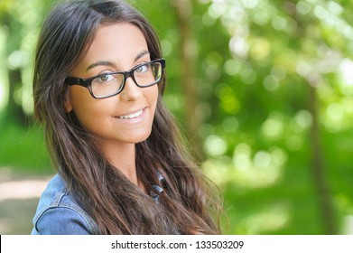 Portrait of beautiful smiling dark-haired young woman, against summer green park.