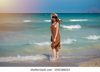 Portrait of beautiful smiling European girl in a bonnet hat against amazing wavy sea. She is on her summer holidays.