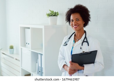 Portrait of beautiful smiling female african american doctor standing in medical office. Health care concept, medical insurance, copy space.