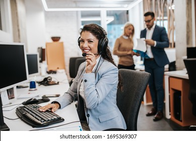 Portrait of beautiful smiling female call-center agent with headset working on support in the office.