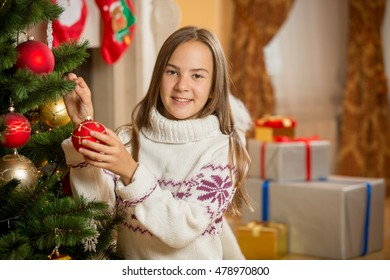 Portrait of beautiful smiling girl decorating Christmas tree with baubles
