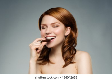 Portrait of a beautiful smiling girl eating a bar of chocolate