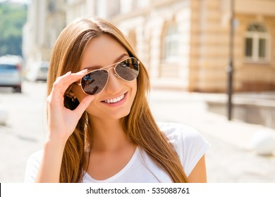 Portrait of beautiful smiling girl in glasses enjoying summer day.