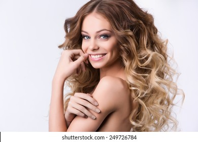 Portrait of beautiful smiling girl with luxuriant hair curling.