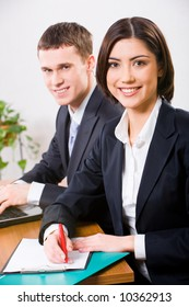 Portrait of a beautiful smiling girl sitting in the office with a confident businessman sitting behind her