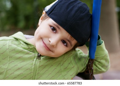 Portrait of beautiful smiling little boy in hat, outdoor shot