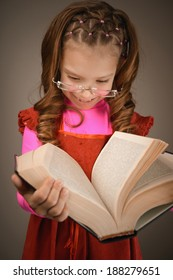 Portrait of beautiful smiling little girl in red dress and with book in studio