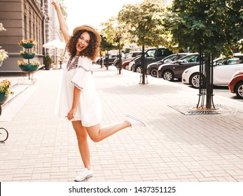 Portrait of beautiful smiling model with afro curls hairstyle dressed in summer hipster white dress. Sexy carefree girl posing in the street background. Trendy funny and positive woman having fun
