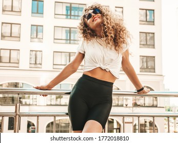 Portrait of beautiful smiling model with afro curls hairstyle dressed in summer hipster clothes.Sexy carefree girl posing in the street background. Trendy funny and positive woman having fun - Shutterstock ID 1772018810