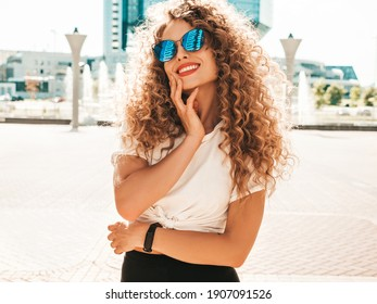 Portrait of beautiful smiling model with afro curls hairstyle dressed in summer hipster clothes.Sexy carefree model posing in the street background. Trendy funny and positive woman having fun - Shutterstock ID 1907091526