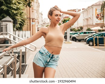 Portrait of beautiful smiling model dressed in summer hipster  jeans shorts. Trendy female posing in the street background. Funny and positive woman having fun in sunglasses. Playing with her hair