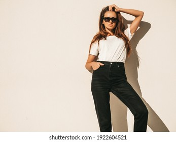Portrait of beautiful smiling model in sunglasses. Female dressed in summer hipster white T-shirt and jeans.Posing near wall in the street. Funny and positive woman having fun outdoors