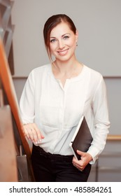 Portrait of beautiful smiling nice young white Caucasian business woman with blue eyes wearing white office blouse shirt and black pants, looking in camera, slavic Russian European face