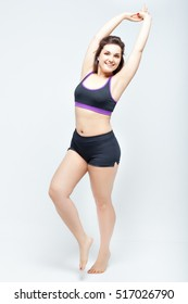 Portrait of beautiful smiling plump woman in a sports underwear on a white background