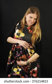 portrait of a beautiful smiling pregnant long haired blond girl hugging her belly wearing a black dress with colorful flowers isolated on black