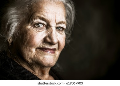 Portrait of a beautiful smiling senior woman over dark background.