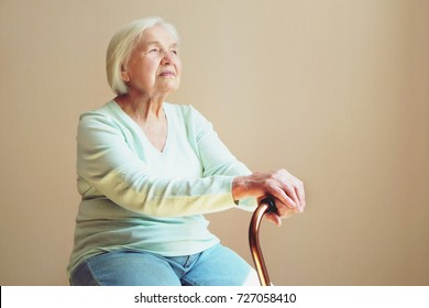 Portrait of a beautiful smiling senior woman with walking cane on light background at home