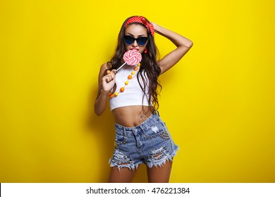 portrait of beautiful smiling sexy girl with a great sports figure in sunglasses in short denim shorts and a white t-shirt. pin-up style. girl holding a big candy on a yellow background