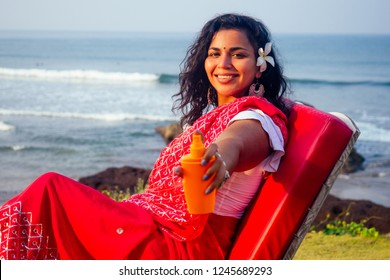 portrait of a beautiful and smiling snow-white smile indian woman black curly hair and dark skin in a red sari holding bottle of sunscreen spray on beach.girl enjoying spf body paradise vacation