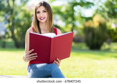 Portrait of a beautiful smiling student reading a book