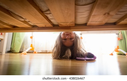 Portrait of beautiful smiling teenage girl looking under the bed for slippers
