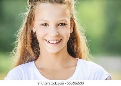 Portrait of beautiful smiling teenage girl in white blouse, against green of summer park.
