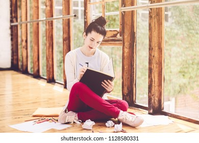 Portrait of beautiful smiling white Caucasian young brunette woman student female artist sitting on floor in college university, drawing sketching. Person at work. Hobby activity concept