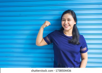 Portrait of beautiful smiling woman in blue flexing her right arm on blue background. Healthy concept. Natural light.