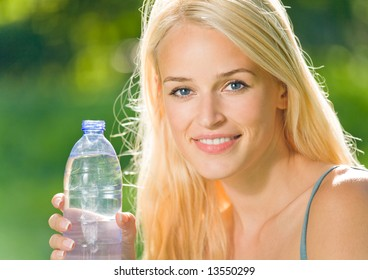 Portrait of beautiful smiling woman with bottle of water, outdoors