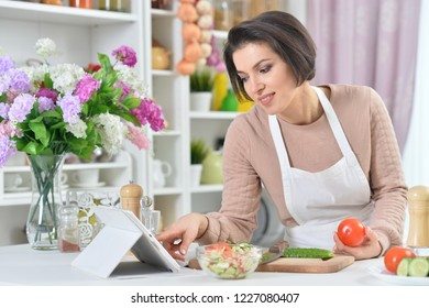 Portrait of a beautiful smiling woman cooking at kitchen