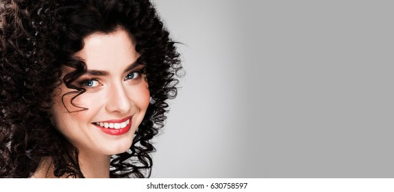 Portrait of beautiful smiling woman with curly hair, gray background