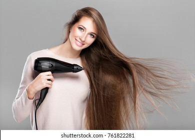 portrait of beautiful smiling woman drying her long hair with dryer over gray background