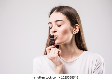 Portrait of beautiful smiling woman enjoy eating chocolate isolated on gray background.