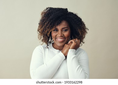 Portrait of beautiful smiling woman with hands clasped against white background