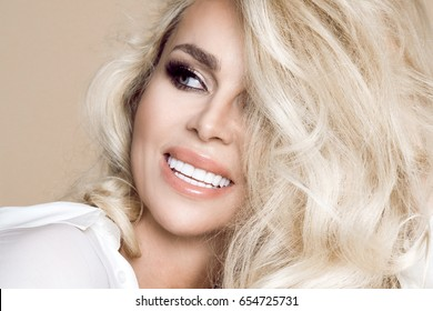 Portrait of a beautiful, smiling woman with long blonde hair and white teeth