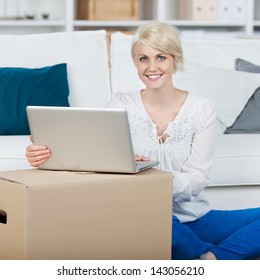 Portrait of a beautiful smiling woman with ??laptop and moving box in the living room