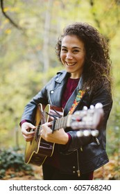 Portrait of beautiful smiling woman playing guitar on forest, fashion lifestyle. Girl wearing black jacket.