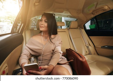 Portrait of beautiful smiling woman sitting on backseat in taxi