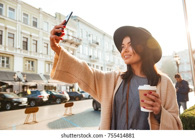 Portrait of a beautiful smiling woman taking a selfie while standing with cup of coffee on a city street