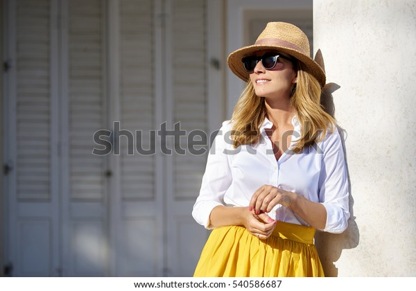Portrait of a beautiful smiling woman wearing straw hat and sunglasses while standing outdoor.