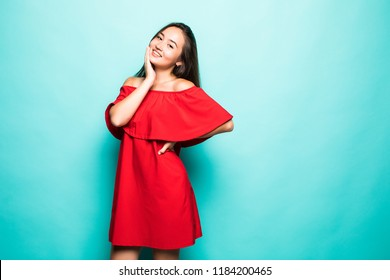 Portrait of beautiful smiling young asian woman standing in cute red dress isolated on blue background