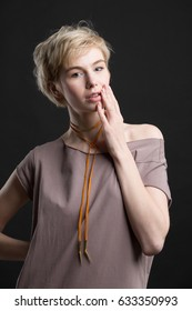Portrait of a beautiful smiling young blond woman wearing orange fashion statement necklace over creamy grey t-shirt on black studio background. Healthy clean skin and perfect makeup. Short hair.