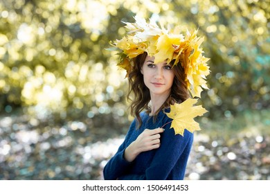 portrait of a beautiful smiling young brunette woman with a wreath of yellow maple leaves on her head and in blue jersey. girl holds autumn maple leaf in hand. Golden forest in the background.