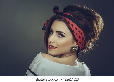 Portrait of a beautiful smiling young fashion female model wearing white blouse, red headband and retro updo hairstyle, looking back over her shoulder against dark background.