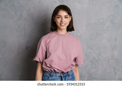 Portrait of a beautiful smiling young girl in casual clothes standing isolated over gray background