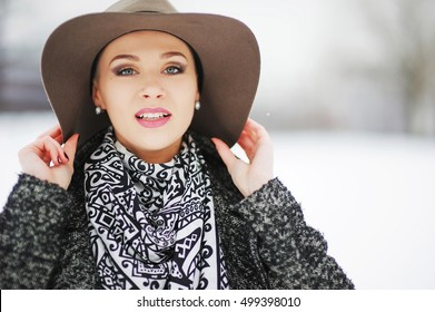 Portrait of a beautiful smiling young girl in  jacket and  hat with  wide brim on  walk in winter Park.