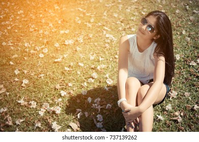 Portrait of a beautiful smiling young girl sitting on grass in a park and looking at camera. She is enjoying nice and sunny spring day in nature,vintage color,copy space