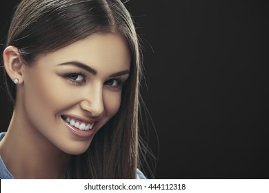 Portrait of beautiful smiling young lady with long straight brown hair posing in studio over dark background with copy space.
