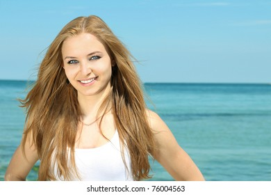 Portrait of a beautiful smiling young lady on the beach background
