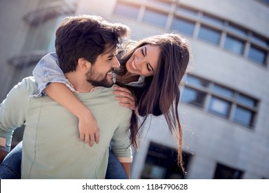 Portrait of beautiful smiling young man and cute woman having fun,hugging and enjoying each other outdoors.